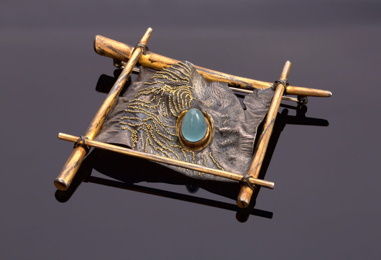 Rectangular brooch with an organic mountain shape in the middle, containing an aquamarine stone